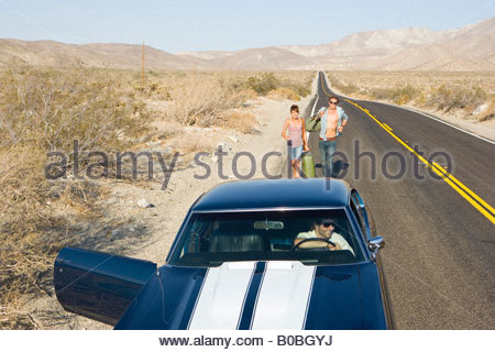 Car with door open for young couple hitchhiking on desert road, elevated view - Stock Photo