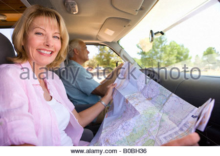 Mature woman with map in motor home with husband, smiling, portrait - Stock Photo