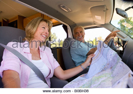 Mature woman with map in motor home by husband, smiling, low angle view - Stock Photo