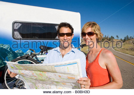 Couple in sunglasses with map by bicycles on back of motor home, smiling, portrait - Stock Photo
