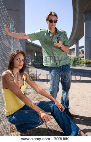 Young couple by fence beneath overpass, man using mobile phone, portrait of woman - Stock Photo