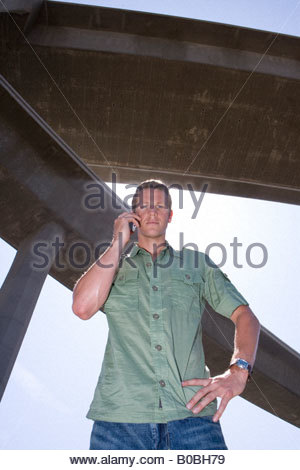 Young man using mobile phone beneath overpass, hand on hip, portrait, low angle view - Stock Photo