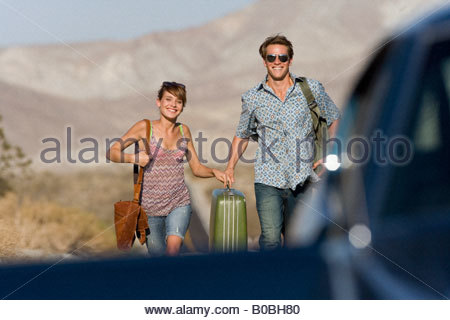 Young couple hitchhiking on open road, walking towards car, smiling, portrait - Stock Photo