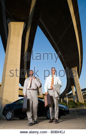 Two businessmen by car with briefcases beneath overpasses, low angle view - Stock Photo