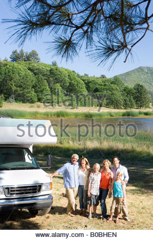 Family of three generations arm in arm by motor home by lake, smiling, portrait, elevated view - Stock Photo