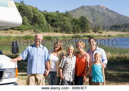 Family of three generations arm in arm by motor home by lake, smiling, portrait - Stock Photo