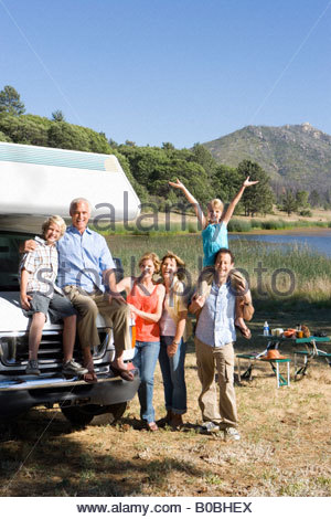 Family of three generations by motor home by lake, smiling, portrait - Stock Photo