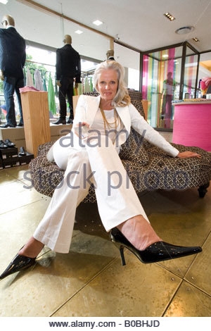 Mature woman in shop, legs crossed, portrait - Stock Photo