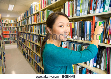 Young woman in library selecting book, close-up - Stock Photo