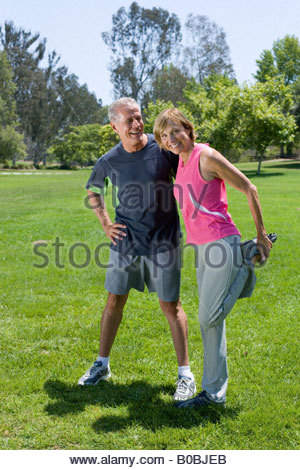 Mature couple exercising in park, woman stretching, portrait - Stock Photo