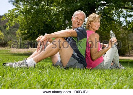Mature couple sitting back to back in park, smiling, portrait, low angle view - Stock Photo