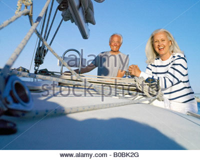 Mature couple on deck of boat, smiling, portrait, low angle view - Stock Photo