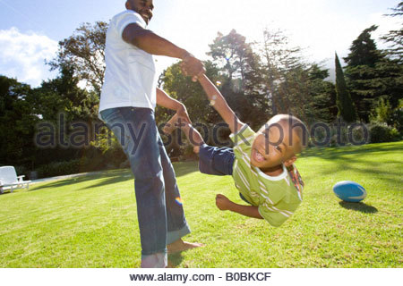 Father swinging son 6-8 years in air outdoors - Stock Photo