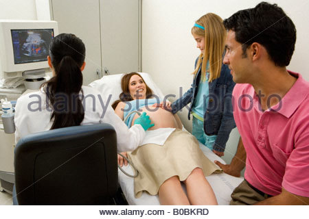 Pregnant woman having ultrasound scan, smiling at daughter  by husband - Stock Photo