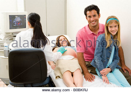 Pregnant woman having ultrasound scan with husband and daughter , smiling, portrait - Stock Photo