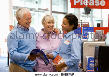 Mature couple shopping for computer, in conversation with saleswoman, smiling - Stock Photo
