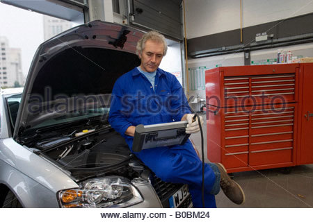 Mechanic with diagnostic computer on car with open bonnet - Stock Photo