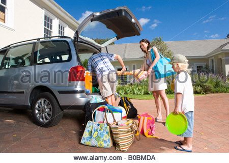 Family of three loading car with luggage, low angle view - Stock Photo