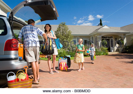 Family of four loading boot of car with luggage, low angle view - Stock Photo