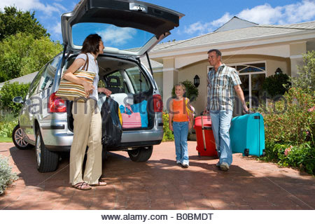 Family of three loading boot of car with luggage, low angle view - Stock Photo