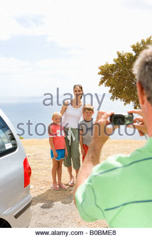 Father taking photograph of mother with son and daughter (6-10) on beach, smiling - Stock Photo