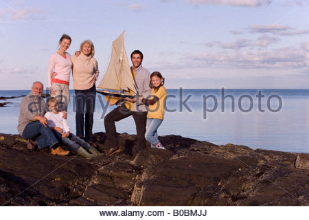 Family holding model sailboat by sea, smiling, portrait, sunset - Stock Photo