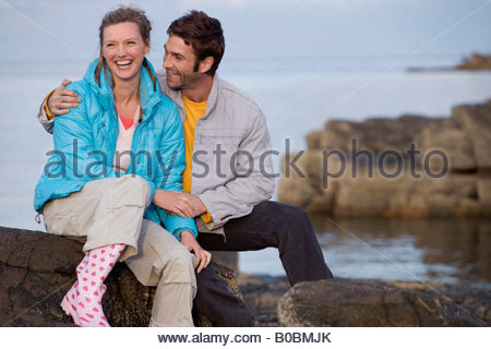 Couple sitting by sea, laughing, sunset - Stock Photo