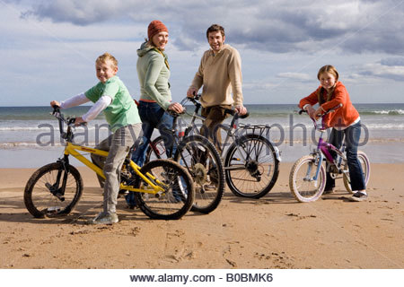 Family of four standing with bicycles on beach, smiling, portrait - Stock Photo