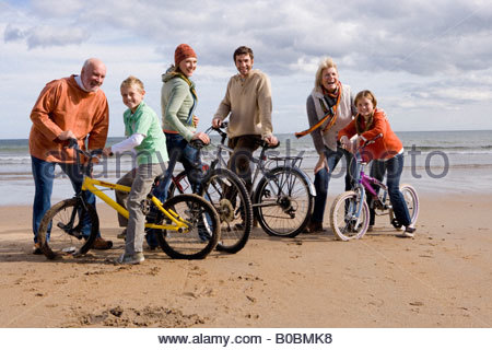 Grandparents with family of four standing with bicycles on beach, smiling, portrait - Stock Photo