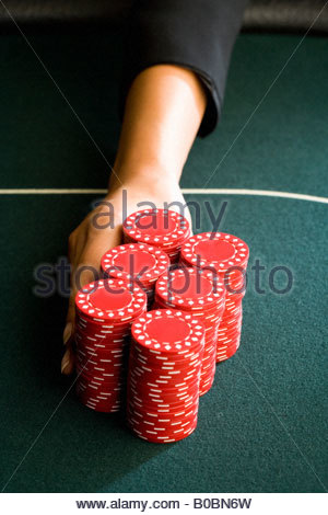 Woman pushing gambling chips onto table, close-up of hand - Stock Photo