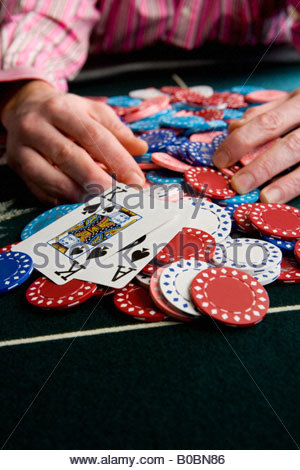 Man collecting pile of gambling chips on table, close-up of winning cards - Stock Photo