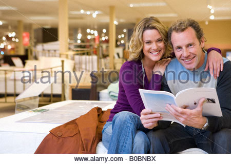 Young couple in furniture shop, woman embracing man with brochure, smiling, portrait - Stock Photo
