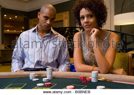 Young man and woman gambling at poker table, portrait - Stock Photo