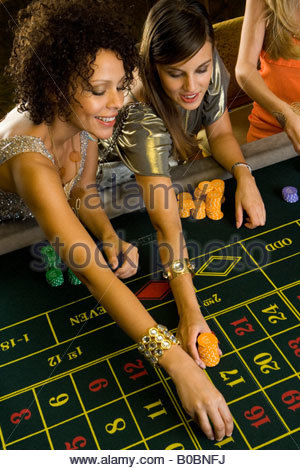 Woman and friend placing gambling chips on roulette table, elevated view - Stock Photo