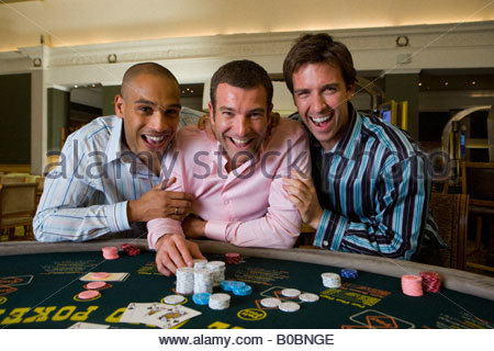 Young man flanked by friends gambling at poker table in casino, smiling, portrait - Stock Photo
