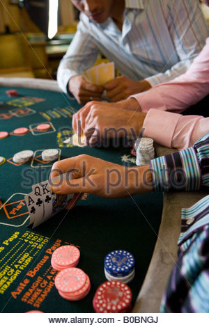 Young men gambling at poker table in casino, section - Stock Photo