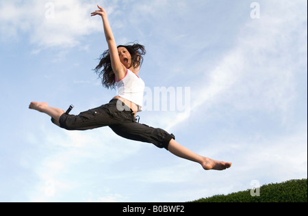 A teenage girl jumping on a trampoline - Stock Photo