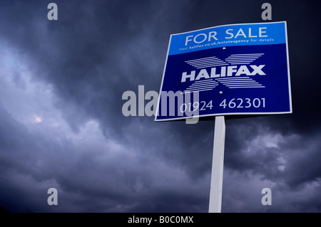 ESTATE AGENT HOUSE FOR SALE SIGN WITH STORMY SKY - Stock Photo