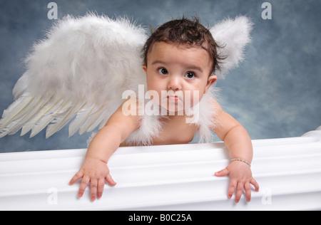 little Hispanic girl wearing angel wings climbing on a white column in a portrait studio - Stock Photo