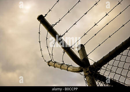 Barbed wire on top of chainlink fence - Stock Photo