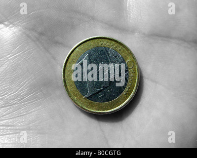 Euro coin in hand - Stock Photo