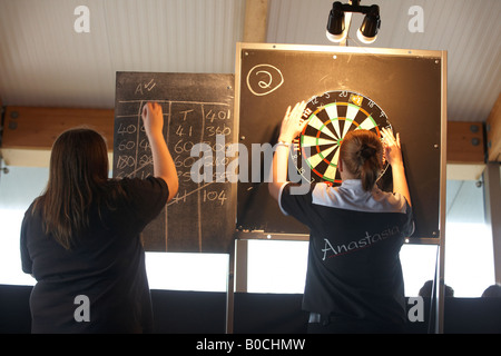 Ladies darts champion Anastasia Dobromyslova retrieves her darts after throwing arrows in a knock out game of 501 - Stock Photo