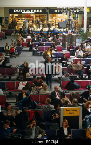 Crowds of passengers in busy Heathrow airport Terminal 4 await the call for flights patiently waiting on BAA seating - Stock Photo
