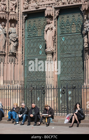 Strasbourg, Notre-Dame gothic cathedral 14th century, tourists sitting on steps of main portal, Virgin Mary with - Stock Photo