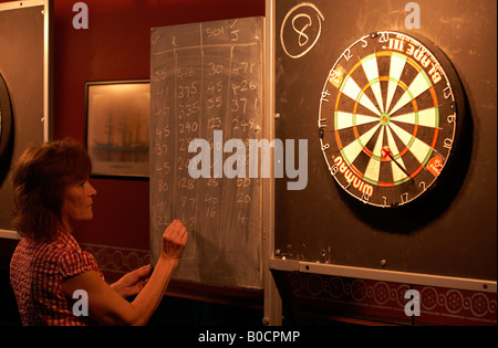 A lady darts player subtracts scores during a game of 501 writing numbers in chalk on the blackboard - Stock Photo