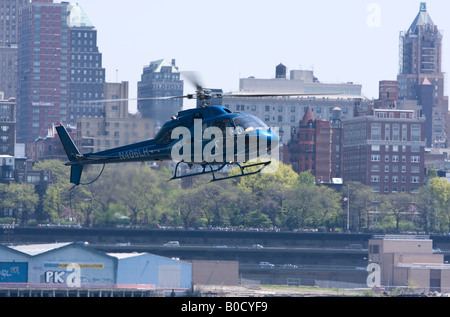 A helicopter drops down over the East River in its approach to the Manhattan Heliport - Stock Photo