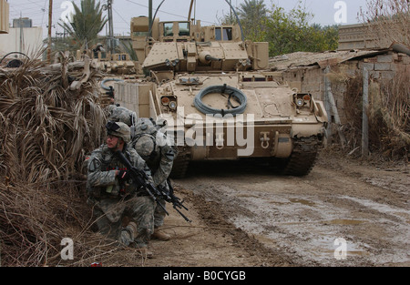 U S Army soldiers with Bravo Company 3rd Battalion 8th Cavalry Regiment wait for orders to conduct a house search. - Stock Photo