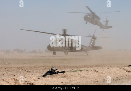 Two U S Army UH 60 Black Hawk helicopters blow up clouds a of dust as they come into a landing zone in Samarra Iraq - Stock Photo