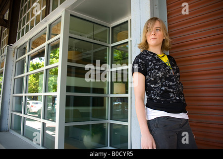 Teen girl leaning against a storefront - Stock Photo