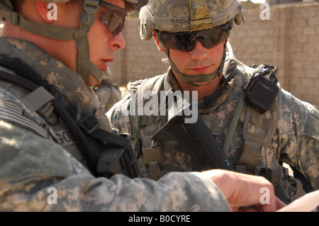 U S Army Staff Sgt Terry Goble left briefs Sgt Robert Klotz prior to a joint patrol through a neighborhood in Shulla - Stock Photo